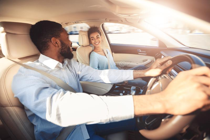 Test drive. Happy couple talking in car stock photography