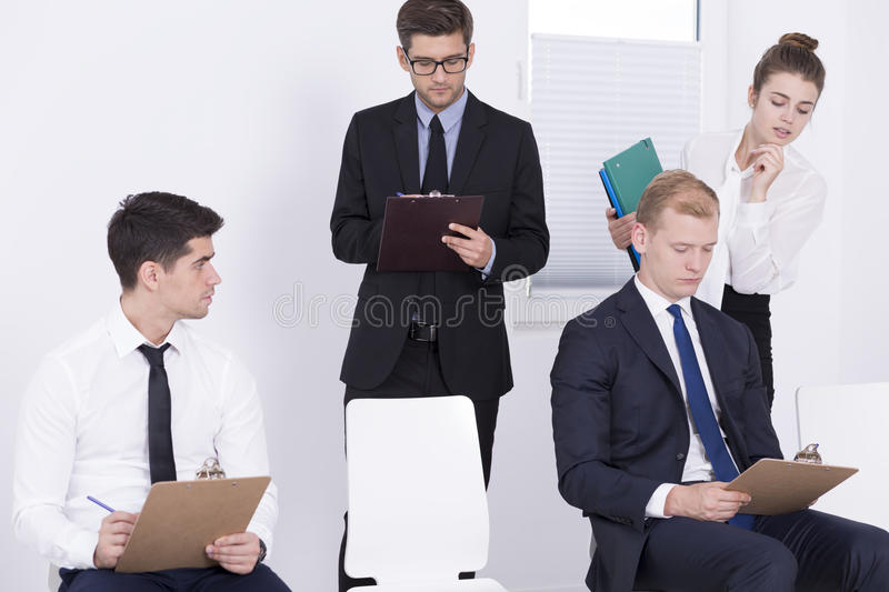 This test is a part of a recruitment. Two men writing qualification test, two HR specialists standing over them, light interior royalty free stock image