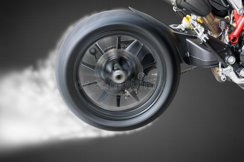 Test the rotation of the wheel of a motorcycle tire. Test the rotation of the wheel and the burning of a motorcycle tire stock photos