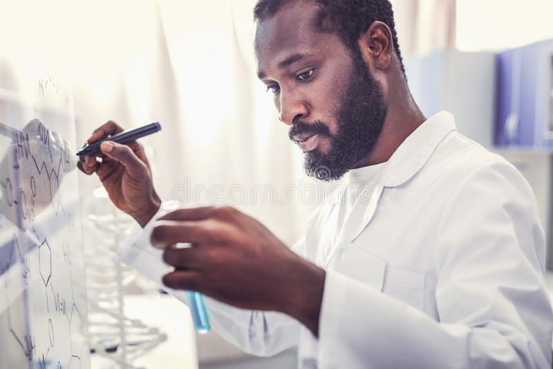 Bearded young physician holding test tube in his hands. Test tube in hands. Bearded young physician feeling very busy while holding test tube with blue substance royalty free stock photo
