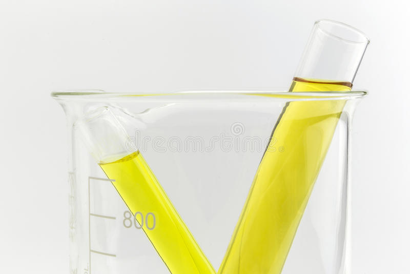 Test tube with yellow liquid (fluid, water) in the beaker royalty free stock image
