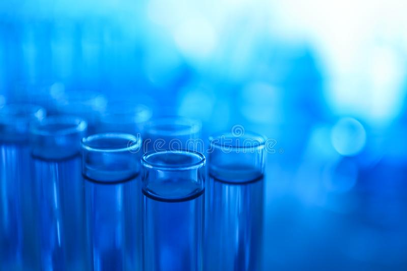 Test tubes with blue liquid on blurred background. Laboratory analysis royalty free stock images