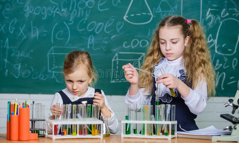 Test tubes with colorful substances. Chemical analysis and observing reaction. School equipment for laboratory. Girls on. School chemistry lesson. School stock image