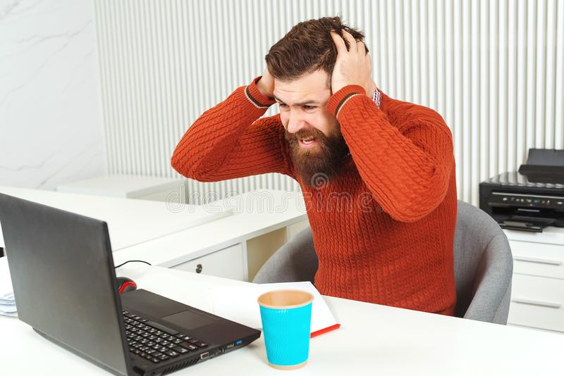 Testa barbuta sollecitata della tenuta dell'uomo con la sua mano nel luogo di lavoro Uomo che esamina computer portatile Responsa immagini stock libere da diritti