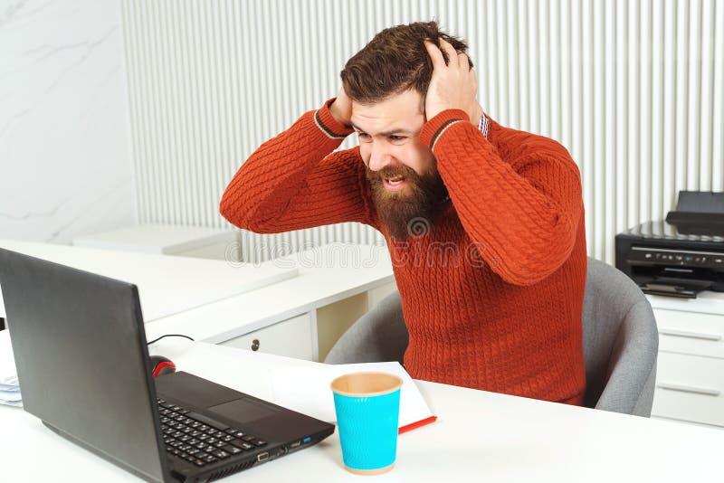 Testa barbuta sollecitata della tenuta dell'uomo con la sua mano nel luogo di lavoro Uomo che esamina computer portatile Responsa immagine stock libera da diritti