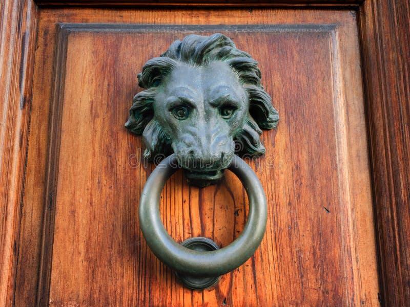 Testa bronzea dei lion's con un battitore di porta dell'anello su una vecchia porta di legno fotografia stock
