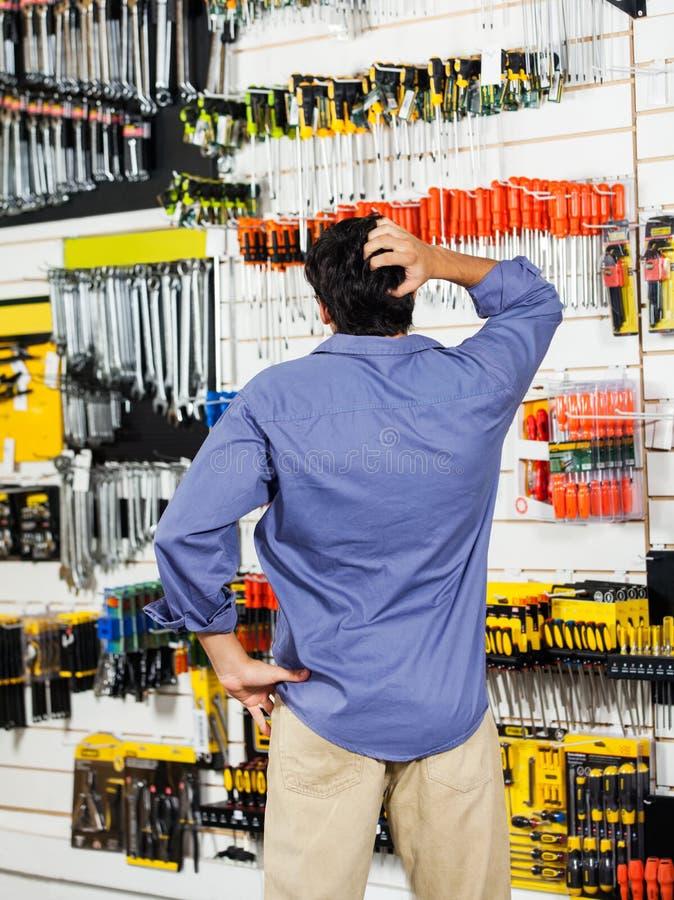 Testa confusa di scratch del cliente nel negozio dell'hardware immagini stock