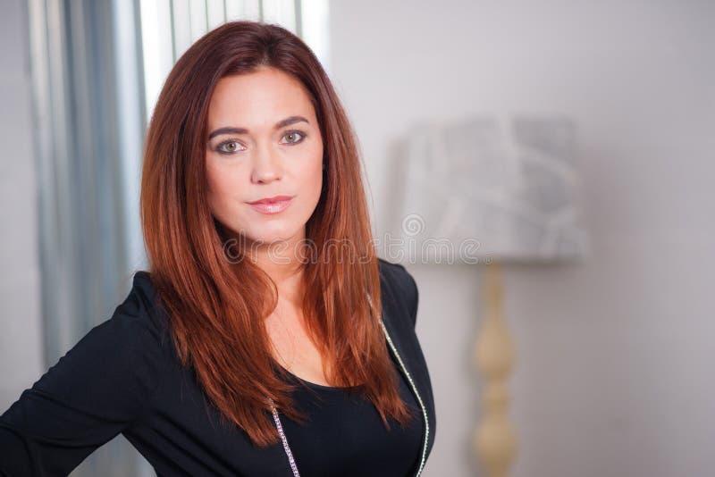 Testa d'uso intellettuale di vetro della donna di affari inclinata fotografie stock libere da diritti