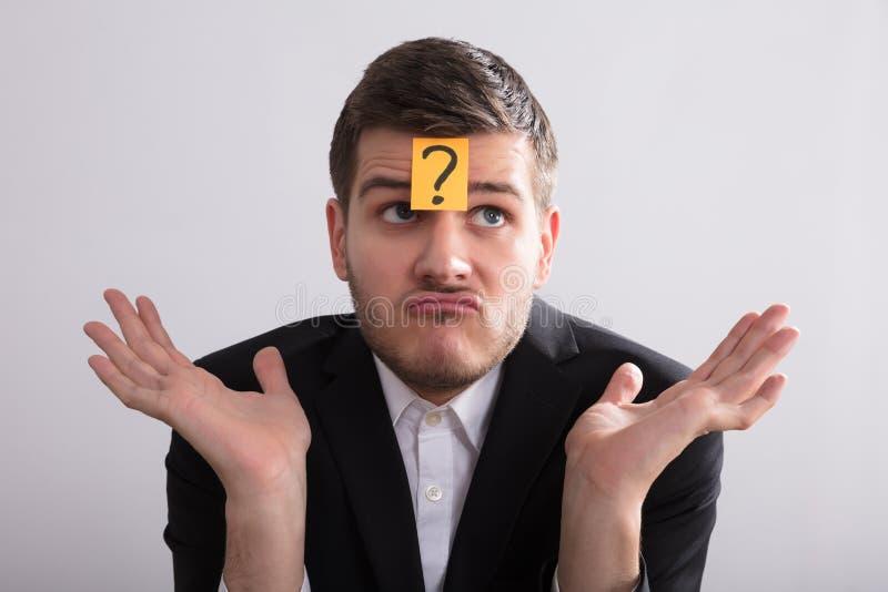 Testa de With Question Mark Sticky Note On His do homem de negócios imagem de stock royalty free