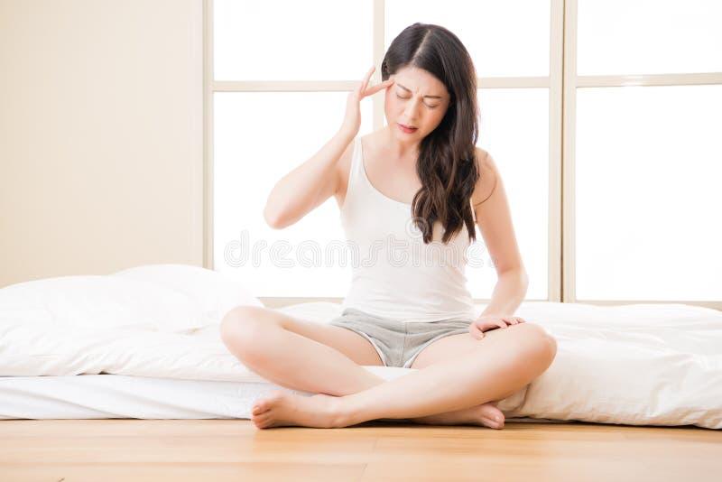 Testa de sofrimento da dor de cabeça e da massagem da mulher asiática bonita fotos de stock