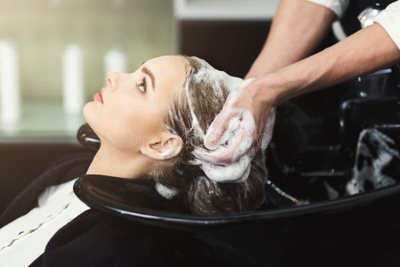 Testa del ` s della donna di lavaggio dell'estetista nel salone di bellezza immagine stock libera da diritti