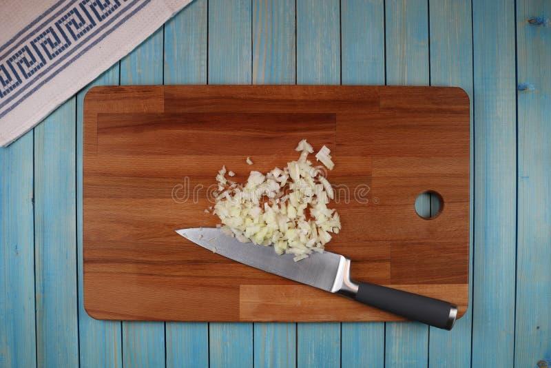 Testa della cipolla nera su un bordo di legno per il taglio delle verdure immagine stock
