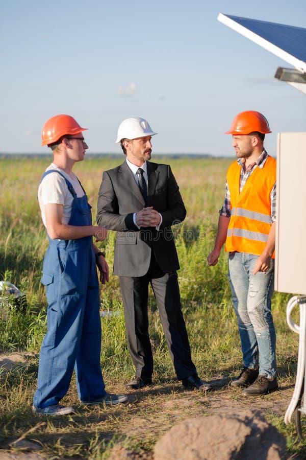Testa della stazione a energia solare che parla con ingegneri immagini stock
