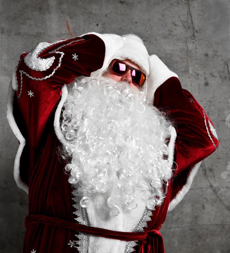 Testa della tenuta del segno di emicrania di Santa Claus con le mani malate Nuovo anno e Buon Natale immagini stock