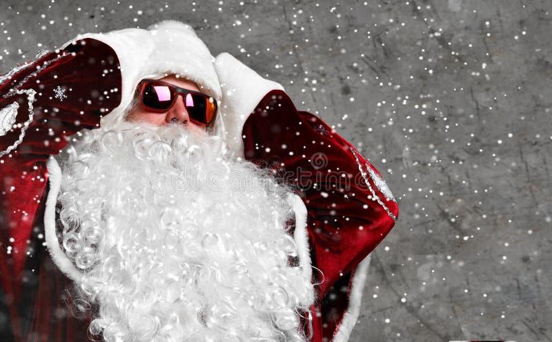 Testa della tenuta del segno di emicrania di Santa Claus con le mani malate Nuovo anno e Buon Natale fotografie stock
