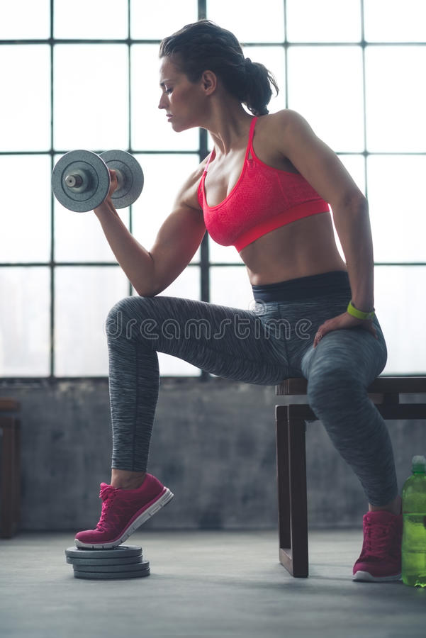 Testa di legno di sollevamento della donna di forma fisica nella palestra del sottotetto fotografia stock