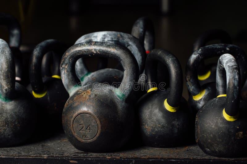 Testa di legno per addestramento del peso nella palestra Kettlebells neri 24kg weightlifting immagine stock