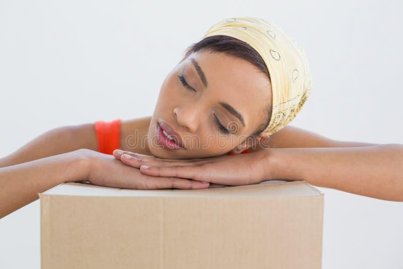 Testa di riposo della giovane donna graziosa sopra le scatole immagini stock libere da diritti