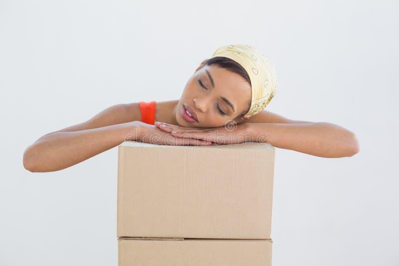 Testa di riposo della giovane donna graziosa sopra le scatole fotografia stock libera da diritti