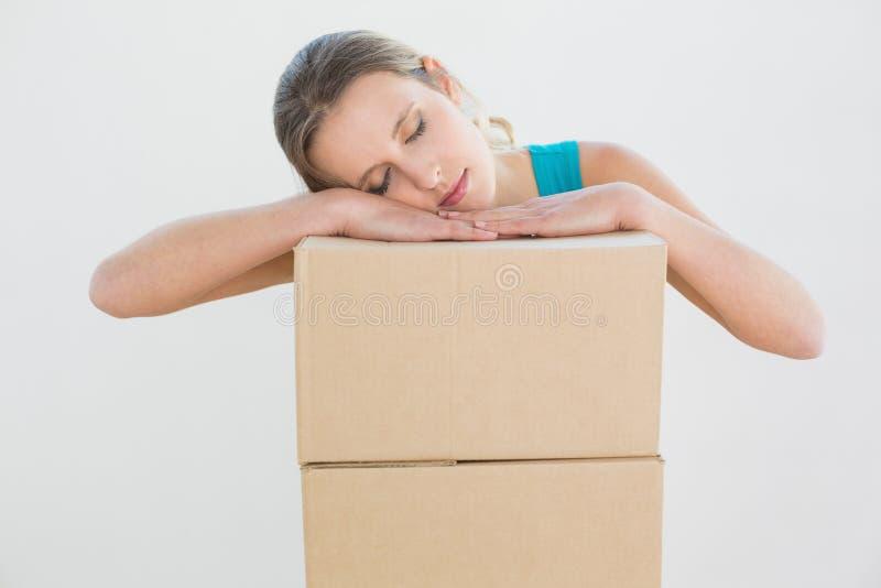 Testa di riposo della giovane donna graziosa sopra una pila di scatole fotografia stock