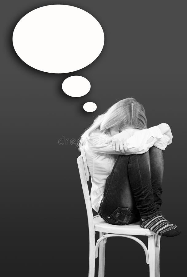 Seduta della giovane donna triste o depressa sulla sedia fotografia stock libera da diritti