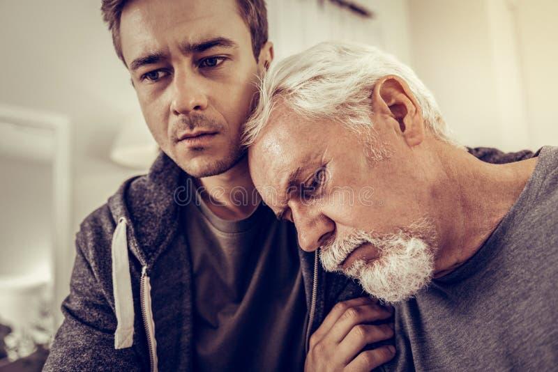 Testa pendente invecchiante dell'uomo sulla spalla di suo figlio immagine stock