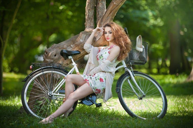 Testarossa bella che si rilassa con la bicicletta nel parco di estate fotografia stock