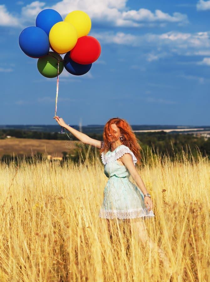 Testarossa della ragazza che corre con gli impulsi alle spighette ed al cielo blu gialli fotografia stock