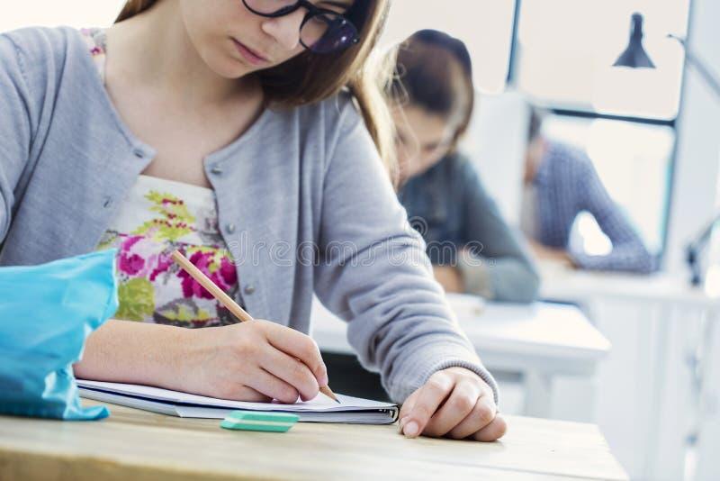 Teste da escrita da menina do estudante na sala de aula imagens de stock
