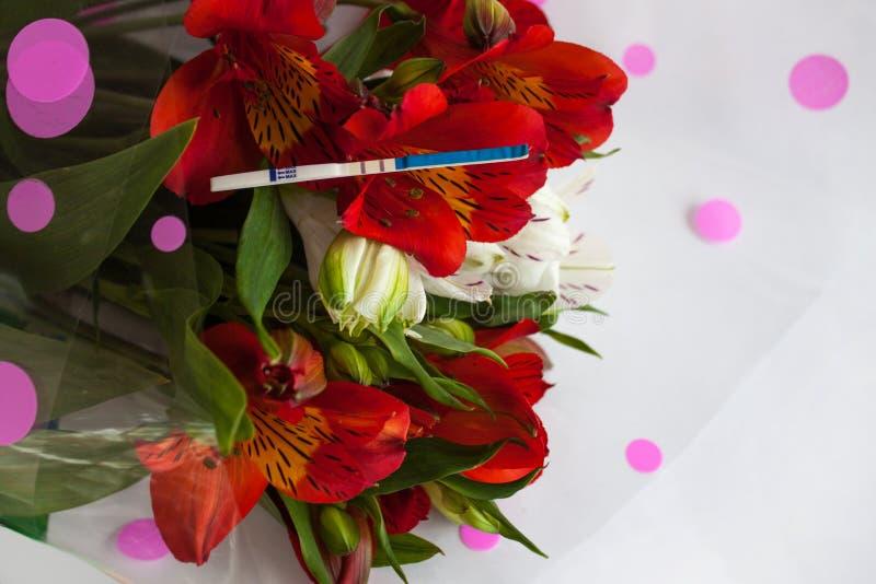 Teste de gravidez positivo com um ramalhete de flores do alstroemeria imagem de stock