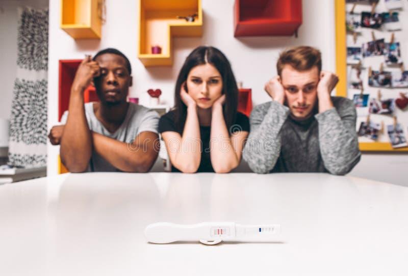 Teste de gravidez positivo, três povos, poligamia fotos de stock