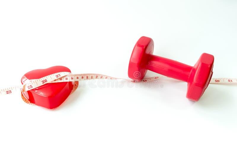 Teste di legno rosse del primo piano con nastro adesivo di misurazione intorno a cuore rosso immagine stock