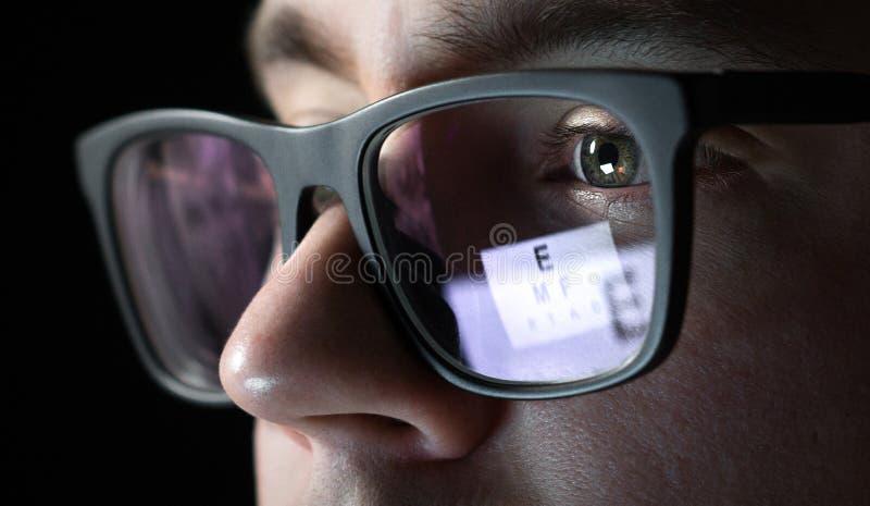 Teste do olho e conceito do exame Feche acima do homem com vidros imagem de stock