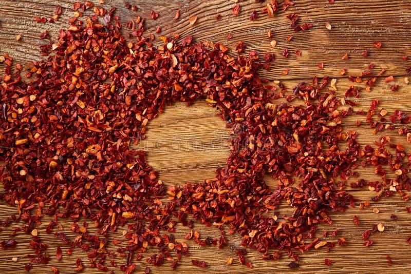 Teste padrão abstrato de flocos frios encarnados secados no fundo de madeira rústico, vista superior, close-up, macro, foco selet fotografia de stock royalty free