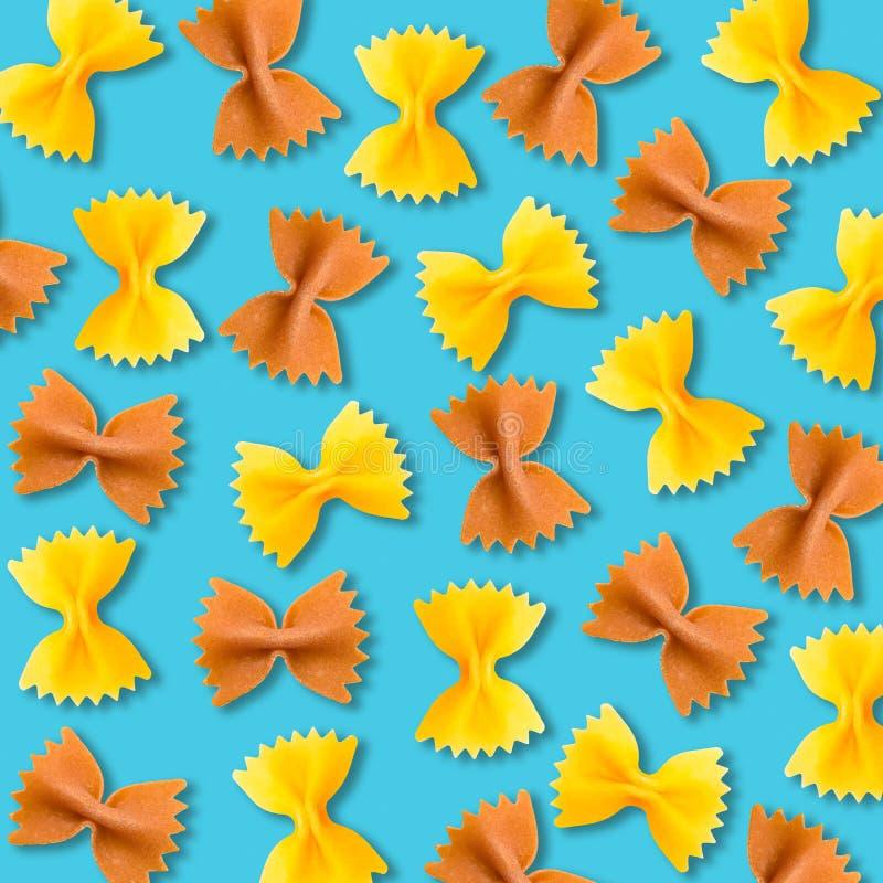 Teste padrão amarelo e marrom da massa do farfalle no fundo vibrante de turquesa fotografia de stock