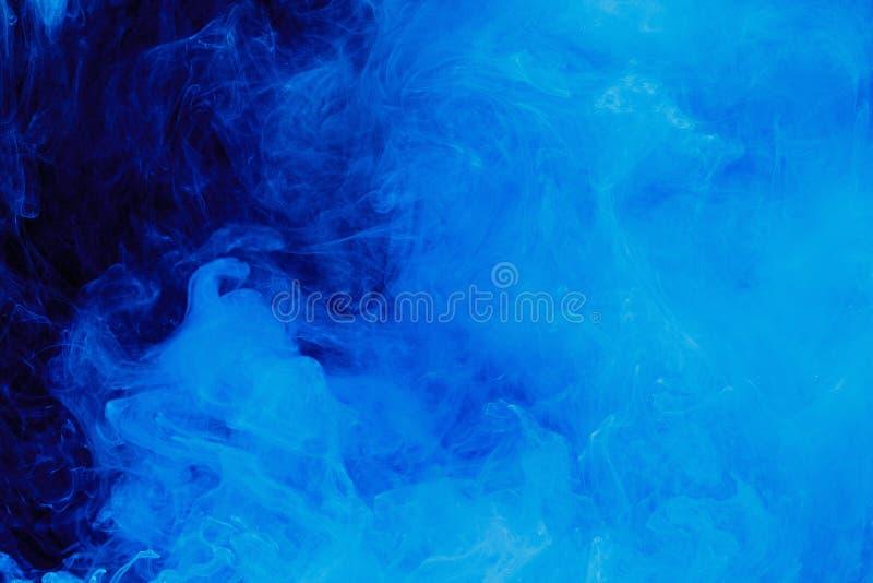 Teste padrão azul abstrato da nuvem do fumo branco em um fundo preto fotografia de stock