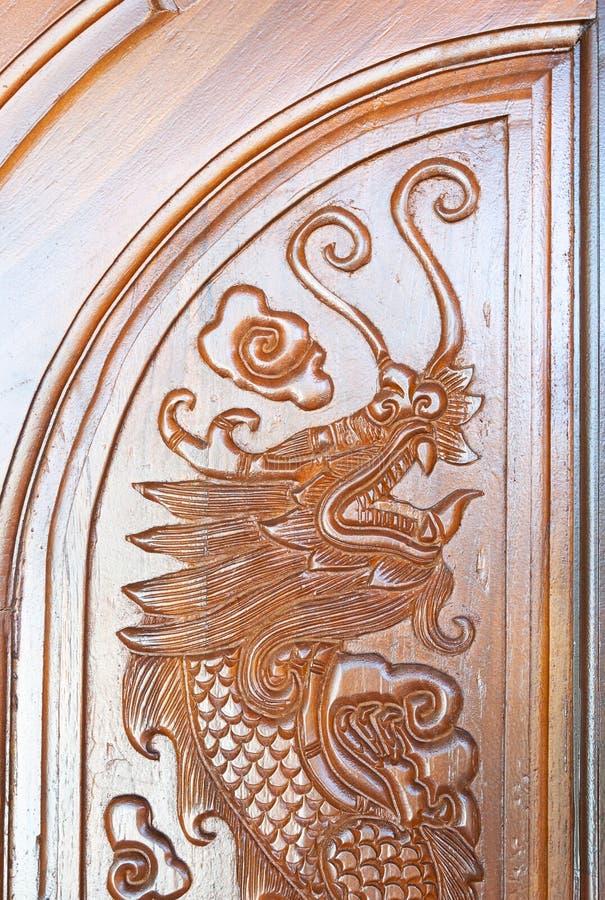 Teste padrão cinzelado do dragão na porta fotos de stock
