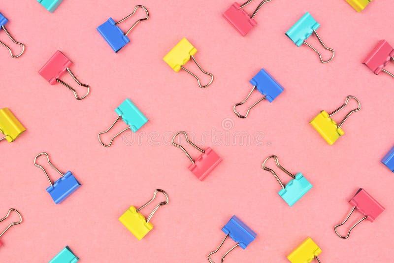 Teste padrão colorido colado do clipe de papel em um fundo cor-de-rosa imagens de stock