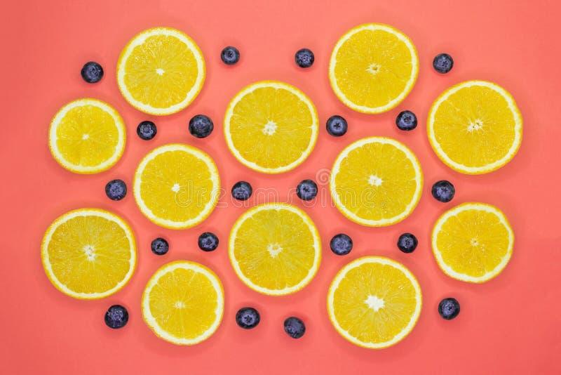 Teste padrão colorido do fruto de fatias e de mirtilos alaranjados frescos no fundo coral imagens de stock