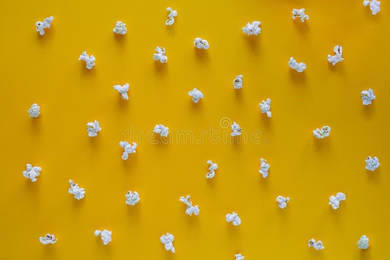 Teste padrão da pipoca no fundo amarelo Vista superior Contraste o conceito pipoca no fundo da cor fotografia de stock