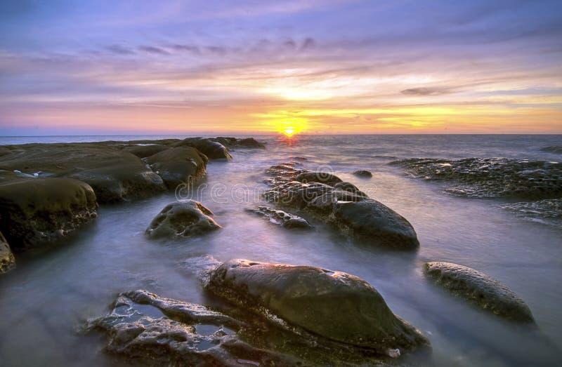 Teste padrão da rocha durante o por do sol/nascer do sol na ponta de Bornéu, Sabah, Mal fotografia de stock