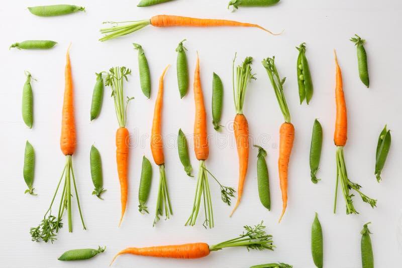 Teste padrão das cenouras cruas e das ervilhas verdes foto de stock