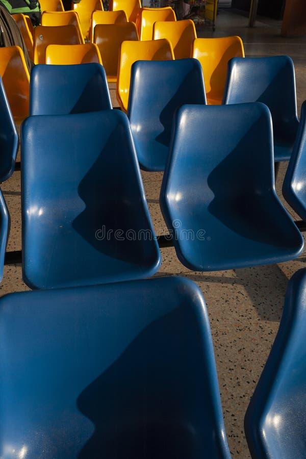 Teste padrão de assentos azuis e amarelos na estação de ônibus imagens de stock