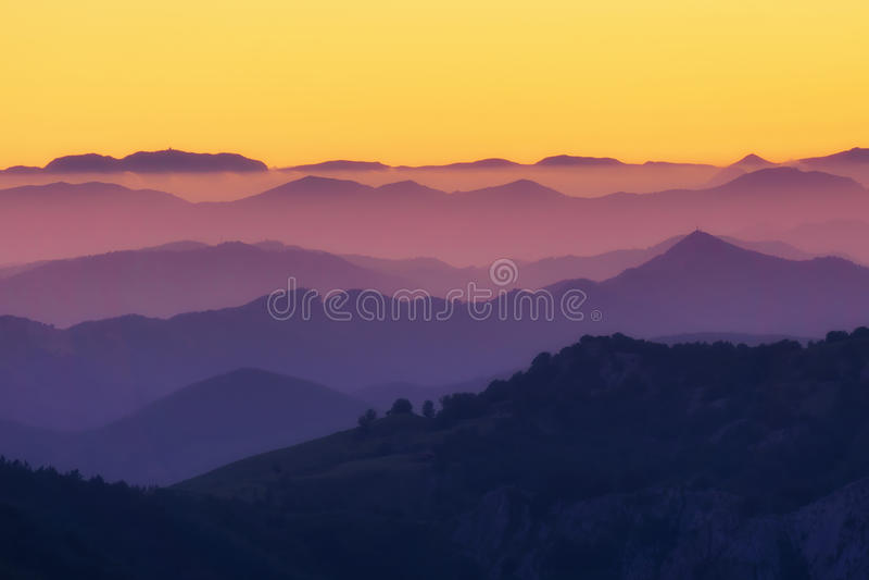 Teste padrão de camadas distantes da montanha no por do sol fotografia de stock royalty free