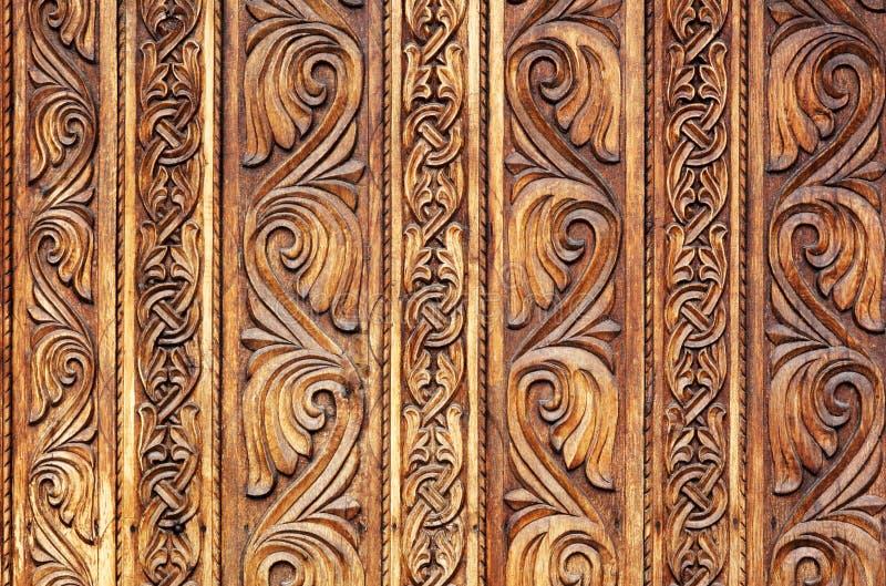 Teste padrão de madeira mão-cinzelado velho em uma porta do monastério foto de stock
