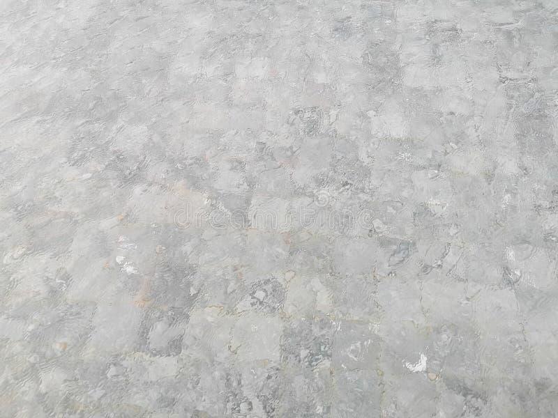 Teste padrão de ondulação da água azul vívida de turquesa na piscina acima das telhas de pedra com luz suave da reflexão da luz d imagem de stock