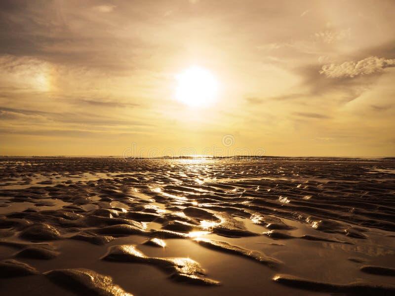 Teste padrão de superfície das ondinhas douradas da areia na praia do por do sol imagens de stock royalty free