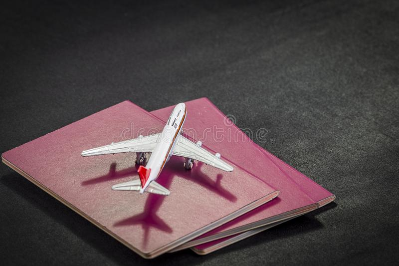Teste padrão do avião em passaportes, em cartões de crédito e na mala de viagem internacionais em um fundo preto foto de stock