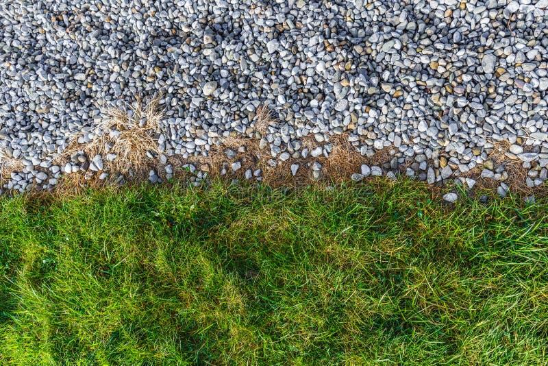 Teste padrão do cascalho cinzento e da grama verde fotografia de stock