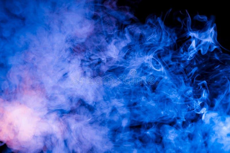 Teste padrão do gelo de um par de aumentação de azul de néon expirado azul do vape em um fundo preto com os córregos encaracolado fotografia de stock royalty free